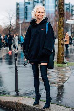Moletom preto oversized como vestido e botas over-the-knee ficam super cool.