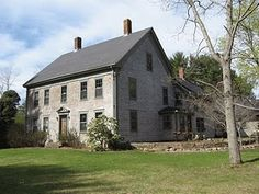 living in a big old colonial. with a fireplace in the kitchen and a view of the water.