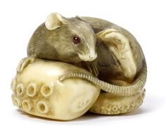 An ivory netsuke of a rat on an octopus tentacle by Chokusai (b.1877), Osaka, early 20th century The small rat seated on the giant curled tentacle, turning to scratch its ear with its hind paw, its tail trailing to one side and its eyes inlaid, the ivory bearing a light stain, signed Chokusai.