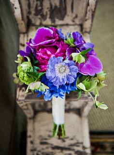Purple, pink, blue and green bridal bouquet | Photo: HBB Photography