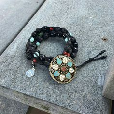 This triple wrap macrame bracelet features black onyx and lava stone, as well as other gemstones. The button is hand painted.