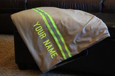 ******* Item is made and ready to ship ******* BLANKET INCLUDES A RED FLEECE BACKING This blanket is made from new materials that look like real firefighter turnouts/bunker gear. It is made with a cotton poly ripstop material and lime yellow triple trim and red fleece backing. Each blanket is personalized with a name or saying to make them a completely custom item. This is the perfect gift for the firefighter in your life! SIZE Blankets are approximately 80 tall and 60 wide. Perfect for t...