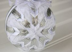 This luminous handmade ornament features sheer white ribbon with white swirls and stripes of silver layered with radiant sheer white ribbon.