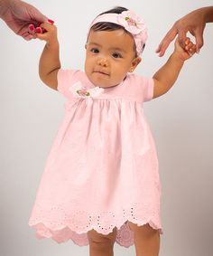 This lovely little frock features an eyelet hem and a bow on the bodice for a look that's sweet as can be. The matching headband blooms with a flower embellishment, topping the set off in lovely charm.