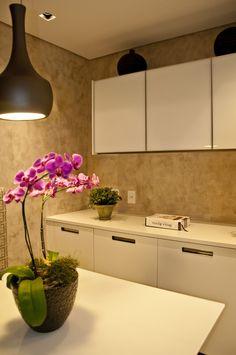Projeto de copa integrada com cozinha. Parede revestida com pintura artesanal, tipo estuco, na cor fendi. Mesa e armários planejados em laca branca com acabamento alto brilho. Pendente Puntoluce. Projeto de decoração e design de interiores para apartamento em estilo contemporâne.