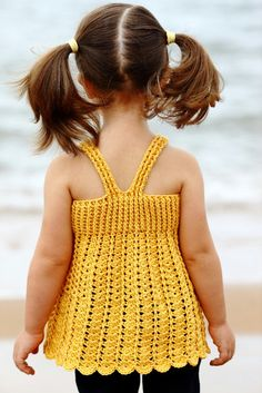 Best 12 Stradbroke is a baby-doll style top featuring racer back straps that button at the front. The ribbed bodice opens up Crochet Toddler Dress, Crochet Baby Dress Pattern, Baby Girl Crochet, Crochet Baby Clothes, Crochet For Kids, Crochet Patterns, Crochet Dress Girl, Gilet Crochet, Crochet Top