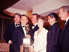 Gregory Peck, John Wayne, Julie Andrews, Jerry Lewis, and Jimmy Stewart posing for a photo at the 1966 Golden Globe awards