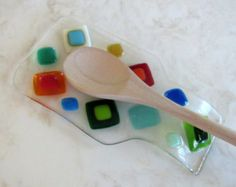 Modern fused glass spoon rest with Shakuf designs original and favorite design.  Blooming Branches in blues, turquoise, emerald, aqua, mint, white, and greens with green branches on a clear background. This dish was Contour fused for a beautiful texture. Each piece retains its individual character, while edges are soft and rounded. Please note that all my items are Handmade so there may be slight color and / or design variations.  A beautiful spoon rest that will add color to your kitchen or…