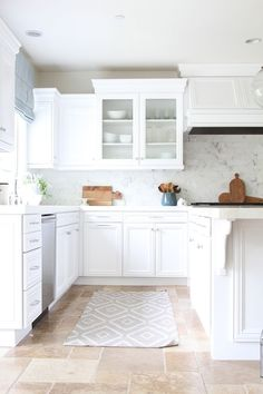 tuscan style floors, marble tile backsplash, mitred marble countertops, white cabinets, neutral beige walls, cutting board, blue linen roman shade, polished chrome/nickel hardware