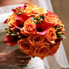 Add Pop of Color  Prev  3/32  Next  Add Pop of Color    For a bold and elegant bouquet to carry down the aisle, pair flame calla lilies, orange roses, and burnt orange hypericum berries.
