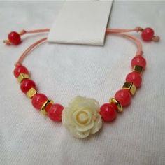 Pulsera: Rosa de mi jardín salmón Materiales: Accesorios en oro golfield, rosa resina, hilo color coral, cuentas de vidrio Valor: $10.000