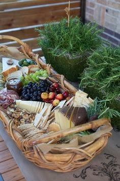 Cheese, crackers, fruits and nuts in a basket