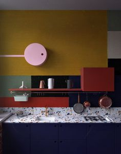 dark blue kitchen with marmoreal top, brass fixtures and postal red shelf