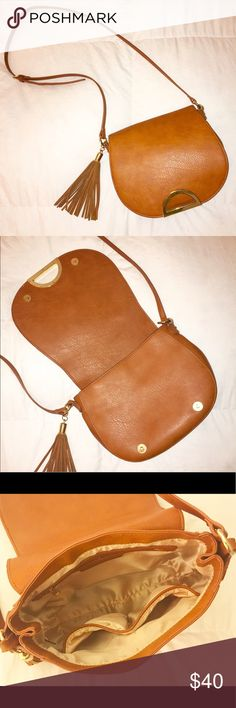 INC Crossbody Saddle Bag This unique, practical bag is in nearly new condition, save the ink mark to the inside flap which is not seen when purse is closed. This purse is a beautiful cognac, with gold and fringe detailing. With the cross body strap, this leather bag is functional and stylish! INC International Concepts Bags Crossbody Bags