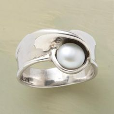 A swath of polished sterling twists round the finger to coddle the cultured white pearl that has been left in its care. Whole and half sizes 5 to 10.
