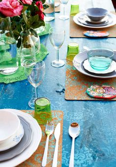 Outdoor dining table set with personalized place mats, colorful dishes, glasses and flowers.