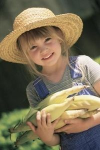 A country girl with fresh picked corn.