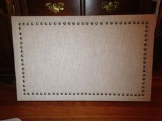 Cork board covered in fabric with brushed nickel nail heads