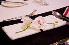 feine Orchidee mit Satinbändchen auf der gefalteten Serviette