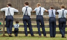 Amish men and boys watch a game of baseball outside the school house in Bergholz, Ohio, US. Many Amish families gathered following the final day of school for a celebration and farewell picnic.