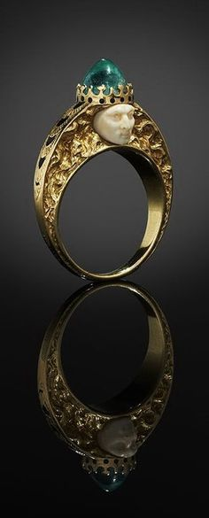 A finger ring by René Lalique in yellow gold, each side centred by a carved ivory face, the ring is surmounted by a cabochon emerald, the setting of the stone formed and enamelled to resemble a crown, the subject's hair sensuously tumbles down the deeply engraved shoulders, the top of the shoulders are decorated with overlapping engraved leaves filled with black enamel.