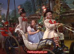 Dorothy and Toto are escorted around Munchkinland in a horse drawn carriage.
