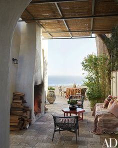 The stone terrace at designer and antiques dealer Richard Shapiro's Malibu, California, home is furnished with rattan and wicker chairs and an early-20th-century octagonal table painted deep red; the large ceramic jar is 16th-century Thai.