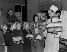 Canadian Army bakers give loaves to Dutch children at Tilburg, December 1944.