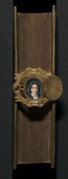 Nineteenth-century English binding of brown goatskin, edged in brass, and with gilt text edges. An inscription inside the book reads: 'Carrie Wilkie the gift of her dear Mother on completing her 18th year.' The woman pictured in the miniature, is possibly Carrie Wilkie's mother. Bound in Oxford or London