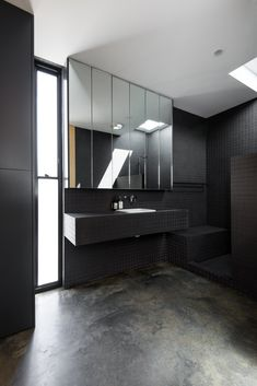 Bathroom Ideas - This modern bathroom features a fully tiled ensuite bathroom, that showcases small black tiles, an open shower with a skylight, a frosted window, and a mirror with hidden shelving. Residential Architect, Architect Design, Ideas Baños, Triangle House, Open Showers, Custom Shelving, Steel Stairs, Timber Deck, Small Hallways