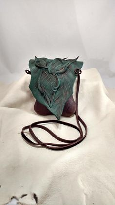 Our smallest leather leaf Forest Purse is made from strong and beautiful chocolate brown and teal bull hide. Measuring approx. 4w x 8h x 2d inches it has plenty of room to carry everything you need: cell phone, keys, small notebook, wallet, iPod, pictures of your grandma etc. We leave