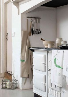love this white country kitchen with white aga, rustic linens, ceramics and vintage finds. Click through for more inspiring contemporary country kitchen ideas