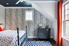 Blue and orange boy's bedroom features a navy painted ceiling over a navy 4 poster bed dressed in stars bedding atop a blue chevron rug facing a window dressed in orange curtains.