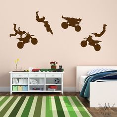 Four dark brown dirt bike wall decals on a beige wall in a children's modern bedroom with a white bed and a white small drawer storage unit. Each vinyl dirt biker is performing a different trick.
