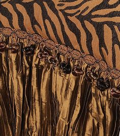 The Madagascar luxury bedding pillow mixes a traditional chenille pattern with a tiger print for the perfect balance. It is finished off with a crushed silk, ball fringe, and carved medallions.