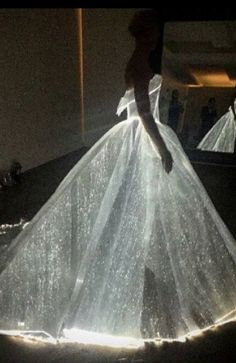 """Posen sourced the  fiber optic woven organza in this dress from France, and there are 30 mini battery packs sewn into the gown's understructure. """"I went through a sequence of stages throughout the process of draping this gown, playing with motion and structure to capture the emotional engineering. The gown is hollow underneath with no tulle – holding its own structure,"""" he said in a statement."""