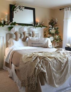 Christmas Bedroom in white and burlap all decked out with holiday greens and Christmas stockings.