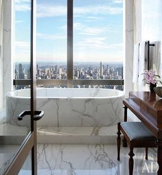Sheathed with Calacatta gold marble, a master bath overlooks Central Park | archdigest.com