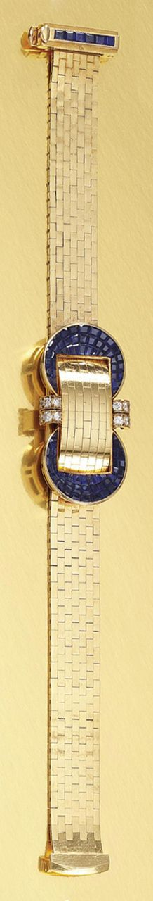 LADY'S SAPPHIRE AND DIAMOND BRACELET WATCH, VAN CLEEF & ARPELS, CIRCA 1952.  Designed to the centre as a stylised buckle invisibly-set with calibré-cut sapphires, highlighted by circular-cut diamonds, opening to reveal a rectangular dial applied with Roman numerals and baton indicators; the cover and bracelet composed of fine brick linking, length approximately 190mm, signed Van Cleef & Arpels and numbered, French assay marks.