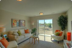 love the green and orange colored throw pillows against white sofa