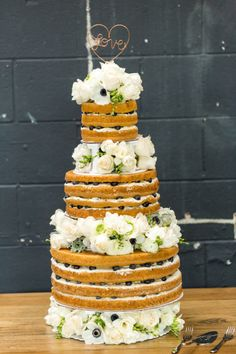 The prettiest naked cake we've ever seen: http://www.stylemepretty.com/little-black-book-blog/2015/05/19/romantic-spring-wedding-at-smog-shoppe/ | Photography: Koman Photo - http://komanphotography.com/