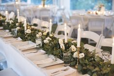 Brass candlestick holders with greenery garland.