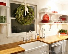 white cabinets, butcher block counters, farmhouse sink and faucet.  I would love open shelving, Ev not so much!