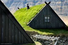 This is one of Iceland's 18th century fishing stations [Pinit and find in on Google maps via www.naturalhomes.org/timeline/fishingstation.htm]. It's built using thick dry stone walls with a timber roof under thick insulating layers of turf. It's the maritime museum just outside Bolungarvik.