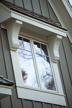 Corbels and window roof detail. White window with gray board and batten wall. #corbels #white #window