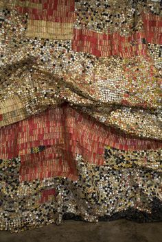 Artists and designers now claim back the right to work with rugged and raw natural materials like sand, twigs, carton, leather, raffia…, and create objects and art with  organic forms and  grainy, fibrous surface textures. On the photo, El Anatsui