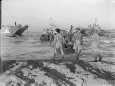 Operation Husky: The Sicily Landings 9-10 July 1943: A tractor comes to the rescue of an armoured vehicle which had stuck in the mud temporarily during the invasion of Sicily, several landing craft can be seen in the background at dawn of the opening day of the invasion.