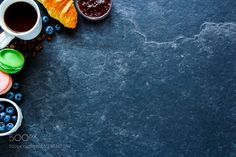 Breakfast concept on table Delicious breakfast set on vintage background. Breakfast of freshly baked croissant coffee in white cup fresh berries strawberry jam and macaroons. Flat lay style. Top view. With copy space by YuliyaGontar