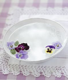 simple plate filled w/ water & flower head