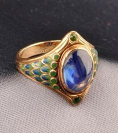 Art Nouveau Sapphire, Demantoid Garnet, and Enamel Ring, Tiffany & Co. bezel-set with a cabochon sapphire measuring approx. 10.20 x 7.70 x 3.72 mm, framed by circular-cut garnets, shoulders with graduating green and blue basse taille enamel accents, incised shank with enamel highlights, size 5 3/4, signed